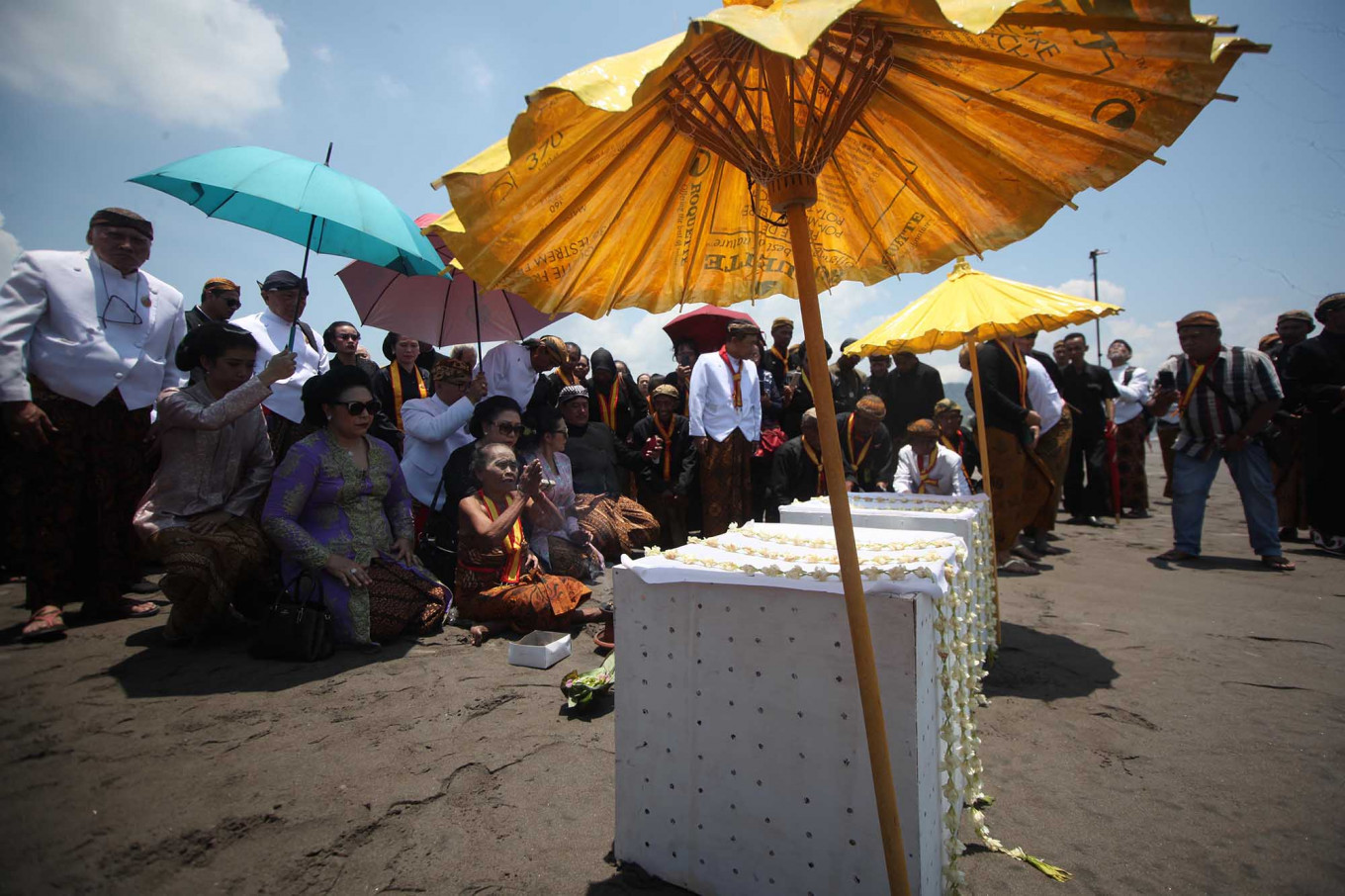 Begging to God: A senior woman royal servant leads a prayer in front of two boxes that will be cast into the sea. JP/Boy T Harjanto