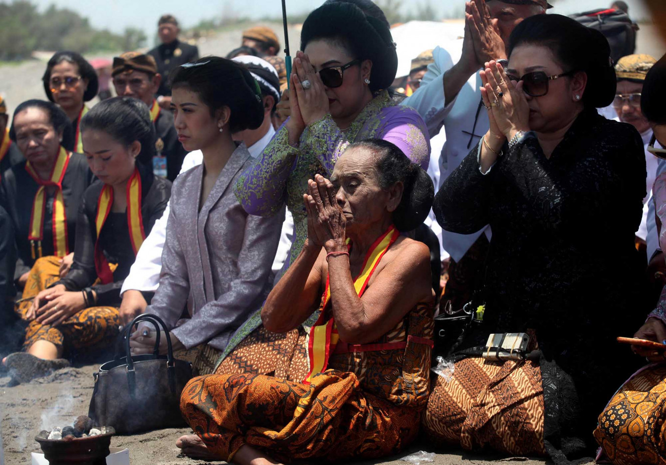 Solemn: Two daughters of Pakubuwono XII, GKR Koes Moertiyah (right) and GKR Koes Indriyah (left), along with a senior female royal servant, pray. JP/ Boy T Harjanto