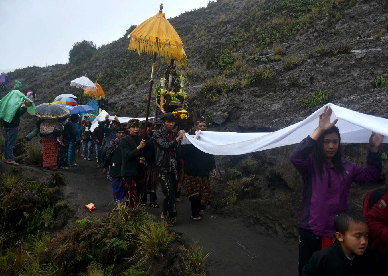 Villagers parade heirlooms and offerings on the way to the Widodaren spring while others hold sheets to catch the rain. JP/Aman Rochman