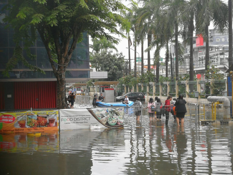 Some officers use a rubber dinghy to transport shop owners to their stores as the parking areas  at the Mangga Dua textile market in Ancol, North Jakarta are deluged by floodwaters on Tuesday.