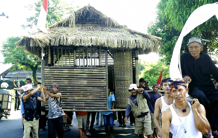 Moving house: The residents of Wates village in Majalengka, West Java, carry a house during an art performance.