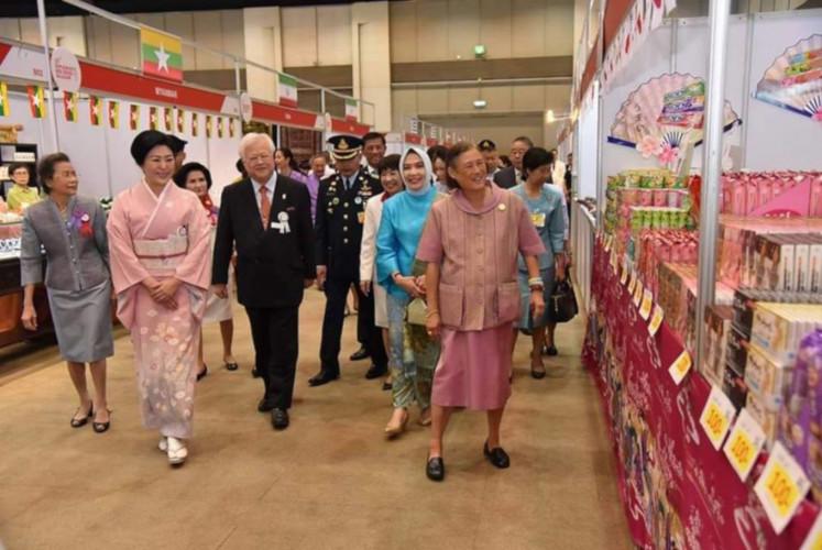 Anita Rusdi, ketua Komite Partisipan Diplomatik (tengah, dengan pakaian biru), menjelajahi stan-stan di samping Putri Mahkota Yang Mulia Maha Chakri Sirindhorn (kanan) di Bazaar Palang Merah Diplomatik di Siam Paragon Hall di Bangkok pada 2 Maret. (Diplomatik ke-52 Komite / Berkas Bazar Palang Merah)