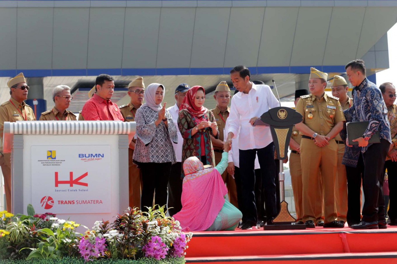 Woman kneels before Jokowi during toll road inauguration. This is her story.