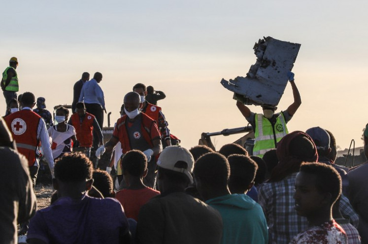 A man carries a piece of debris on his head at the crash site of a Nairobi-bound Ethiopian Airlines flight near Bishoftu, a town some 60 kilometres southeast of Addis Ababa, Ethiopia, on March 10, 2019. A Nairobi-bound Ethiopian Airlines Boeing crashed minutes after takeoff from Addis Ababa on March 10, killing all eight crew and 149 passengers on board, including tourists, business travellers, and