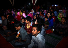 Take your seat: Children and their parents wait for a bioling screening at Ngijo village in Malang, East Java, on February 6, 2019. Free film screenings take place monthliy as requested by the public with 12 movies for children and families. JP/Aman Rochman