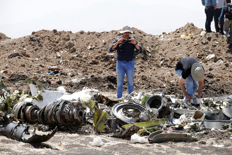 In pieces: American civil aviation and Boeing investigators search through debris at the crash site of Ethiopian Airlines flight ET302 near the town of Bishoftu, southeast of Addis Ababa, on Tuesday.