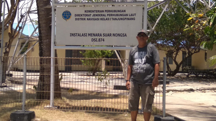 Lighthouse keeper Heriyanto stands in front of his post on Putri Island.
