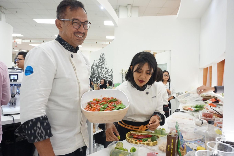 Chef Bara Pattiradjawane menunjukkan hidangan 'sambal colo-colo' dari Maluku. Chef Astrid Enricka Dhita membantunya membuat pasta | Foto: