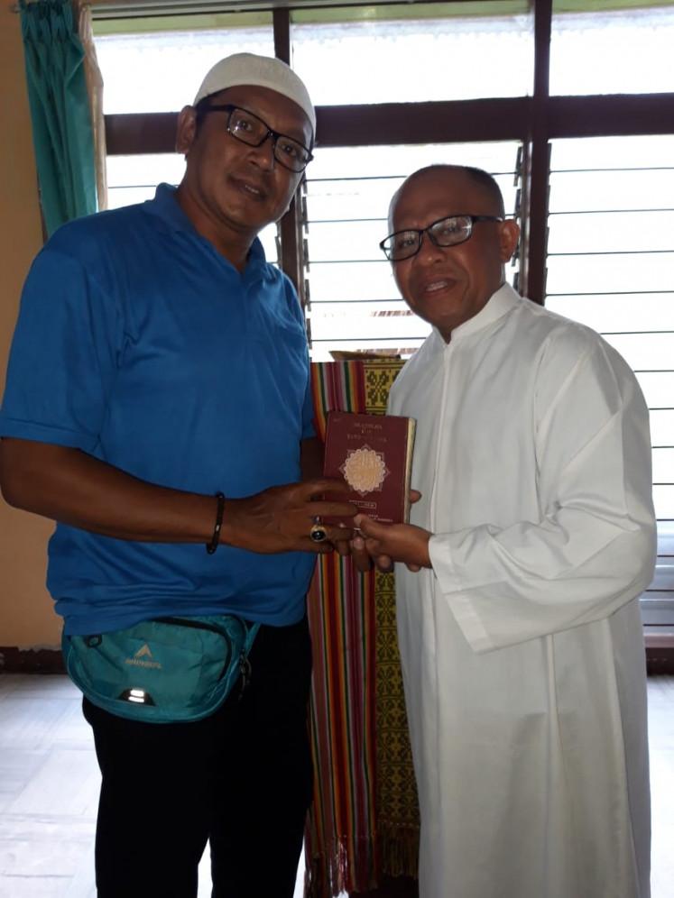 Haji Udin from Taman Baca Mutiara Pelangi Reo in Reo district, Manggarai regency, receives a Quran from West Flores Kompak Le Nuk Institution founder Pastor Wilfridus Babun on March 14.