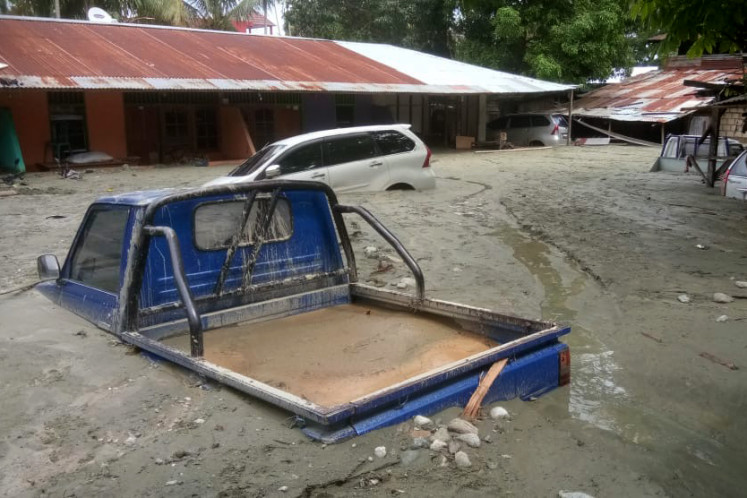 Vehicles are seen immersed in mud after flooding in Sentani, Jayapura, Papua on Sunday.