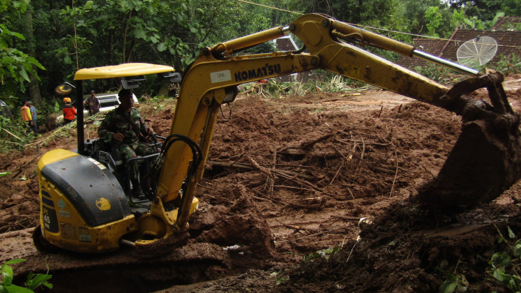 A military officer operates a backhoe to search for victims of flooding and landslides in Imogiri, Bantul, Yogyakarta, on Monday.
