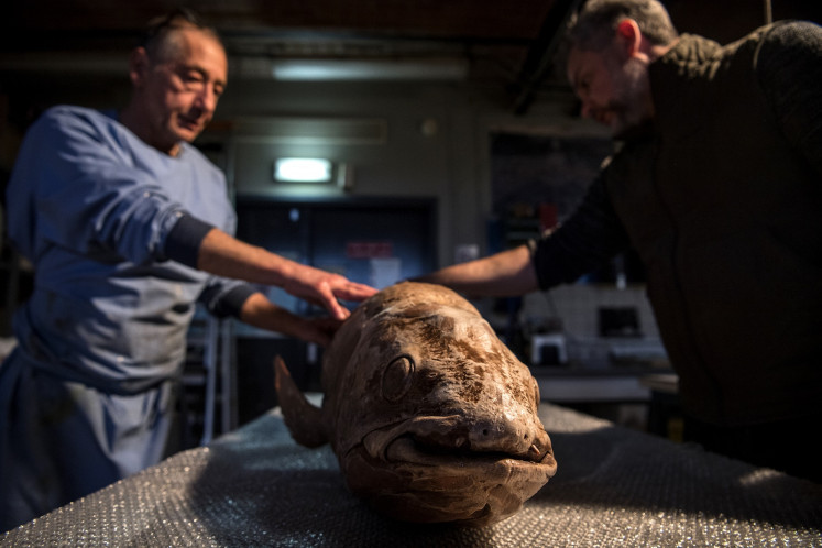 Head taxidermist at the Museum d'Histoire Naturelle Christophe Gottini (L) and taxidermist Vincent Cuisset (R) look at a coelacanth ahead of its restoration work at the Museum d'Histoire Naturelle's (French National Museum of Natural History) taxidermy workshop in Paris on March 12, 2019.