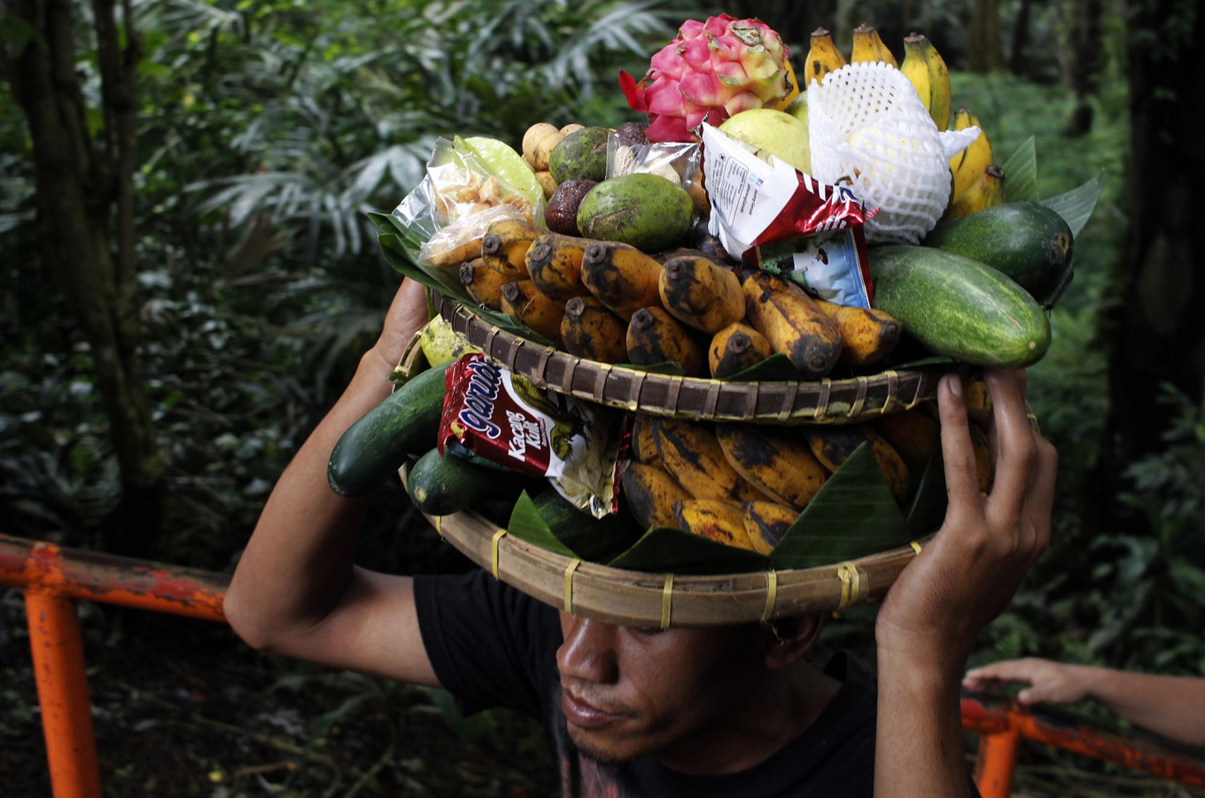 Giving thanks: A Magelang resident carries fruit and snacks. JP/Magnus Hendratmo