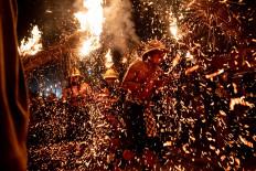Balinese youth walk in the middle of fire during the Mabuwu-Buwu ritual at Punduk Dawa village, Klungkung. JP/Agung Parameswara