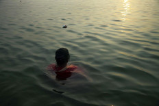 A woman is immersing herself on the Ganges River during the Sunrise, the most important time of the day in Varanasi. JP/Irene Barlian