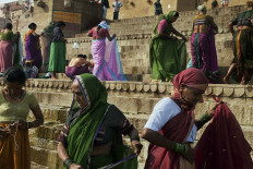 The Ghat is a riot of color as women dressed after puja (worship) ceremony. JP/Irene Barlian