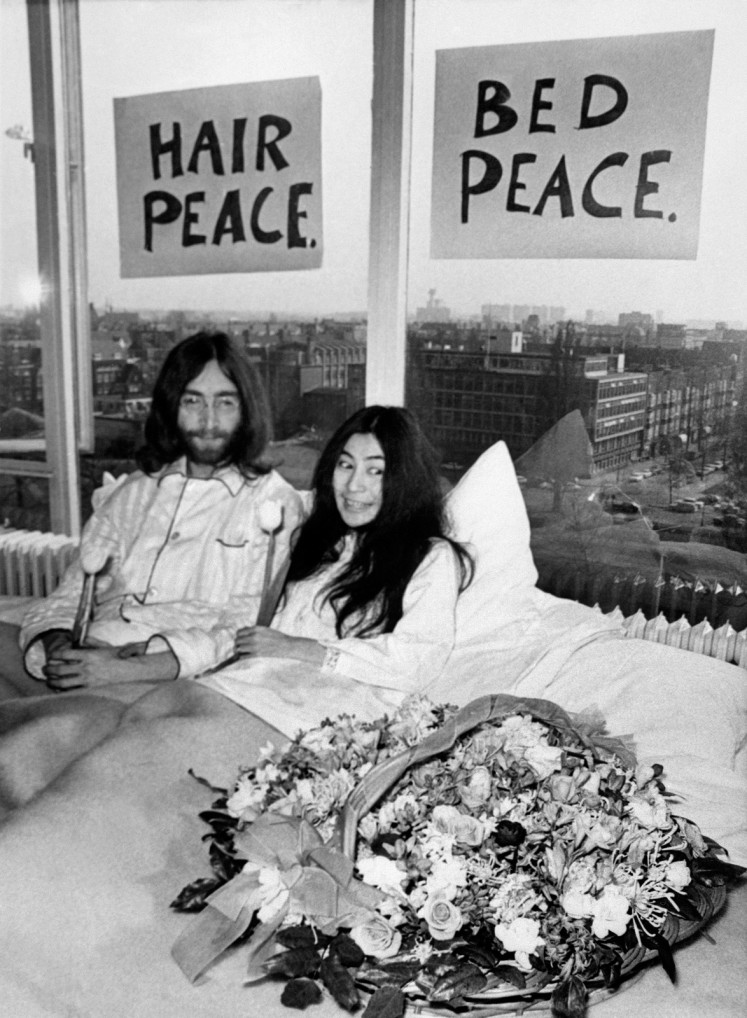 This file photo taken on March 25, 1969 shows Beatles member John Lennon (L) and his wife Yoko Ono receiving journalists in the bedroom of the Hilton hotel in Amsterdam, during their honeymoon in Europe.