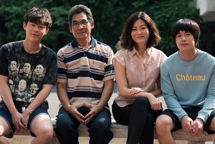 Min (Teeradon 'James' Supapunpinyo, right) poses with his family; his brother Menn (Nutthasit 'Best' Kotimanuswanich, left), father (Roj Kwantham, second left) and mother (Suquan Bulakul, second right).