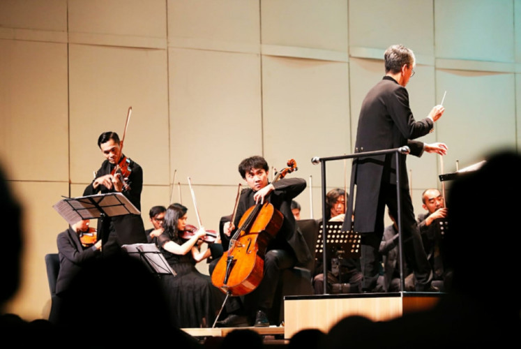 Violinist Danny Artyasanto (left), cellist Dani Kurnia Ramadhan (center) and conductor Budi Utomo Prabowo (right) perform 'Double Concerto in A minor, Op. 102' by Johannes Brahms.