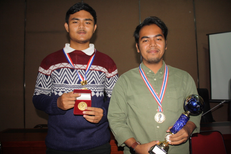 Wahid Nurhayat (left) and Winelda Mahfud Zaidan Haris display their gold medals and trophy at the USU rectorate office in Medan, North Sumatra. The students' plant-based brake pads were recognized at the 22nd Moscow International Salon of Inventions and Innovative Technologies.