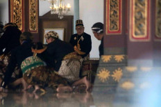 King Paku Buwono XIII sits on his Dampar Kencana throne while courtiers squat walk before him. JP/Maksum Nur Fauzan