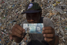 A villager shows off a 5 poundsterling banknote from the imported waste. JP/Sigit Pamungkas