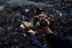 A villager is showing the unsorted waste that will be sold to food home industries for firing material. JP/Sigit Pamungkas