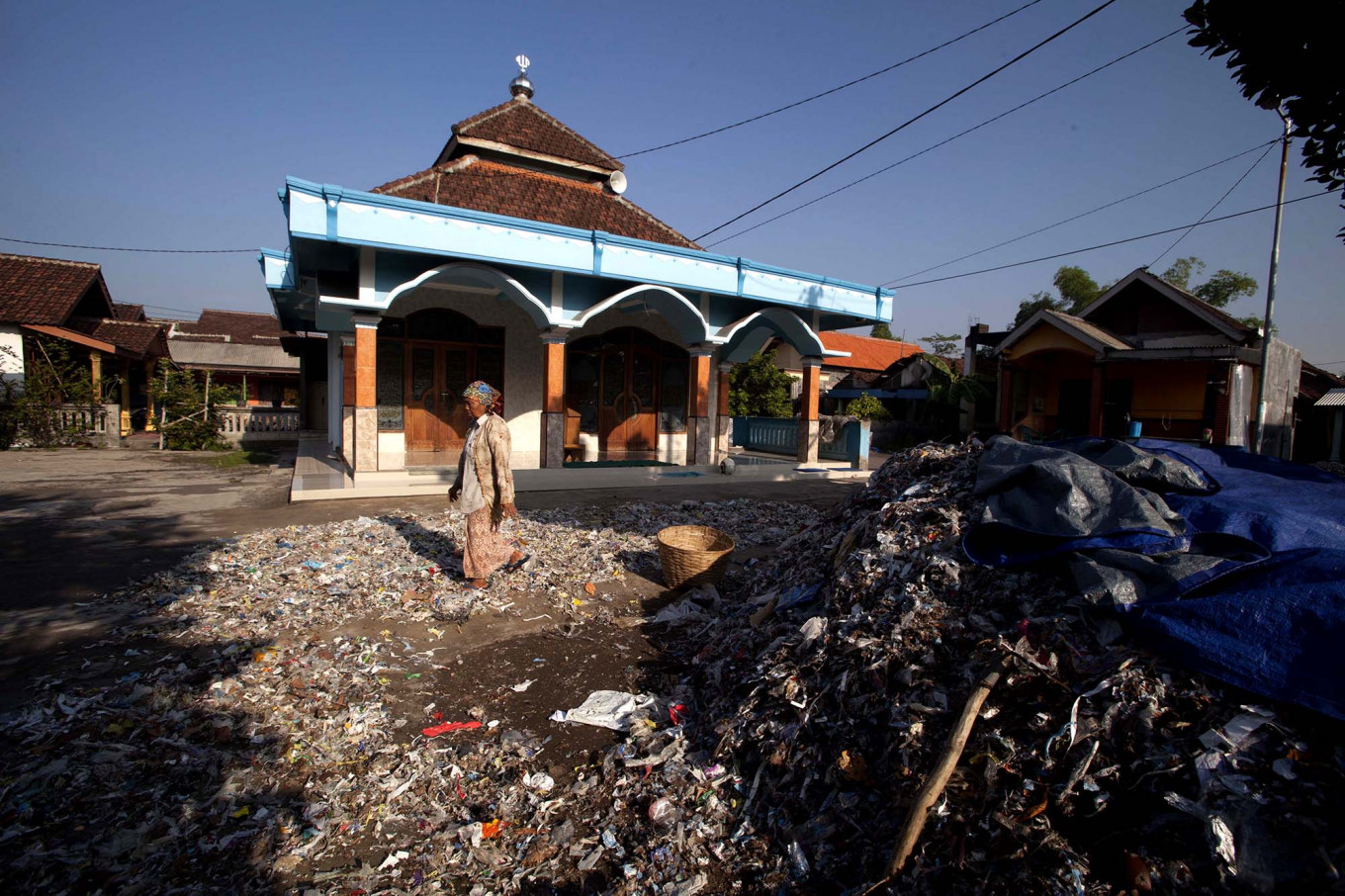An elderly woman is sundrying waste in front of her house and the nearby mosque. JP/Sigit Pamungkas