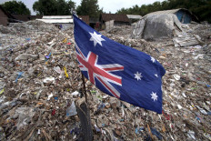 An Australian flag is put upside down at the pile of waste in Bangun village. JP/Sigit Pamungkas