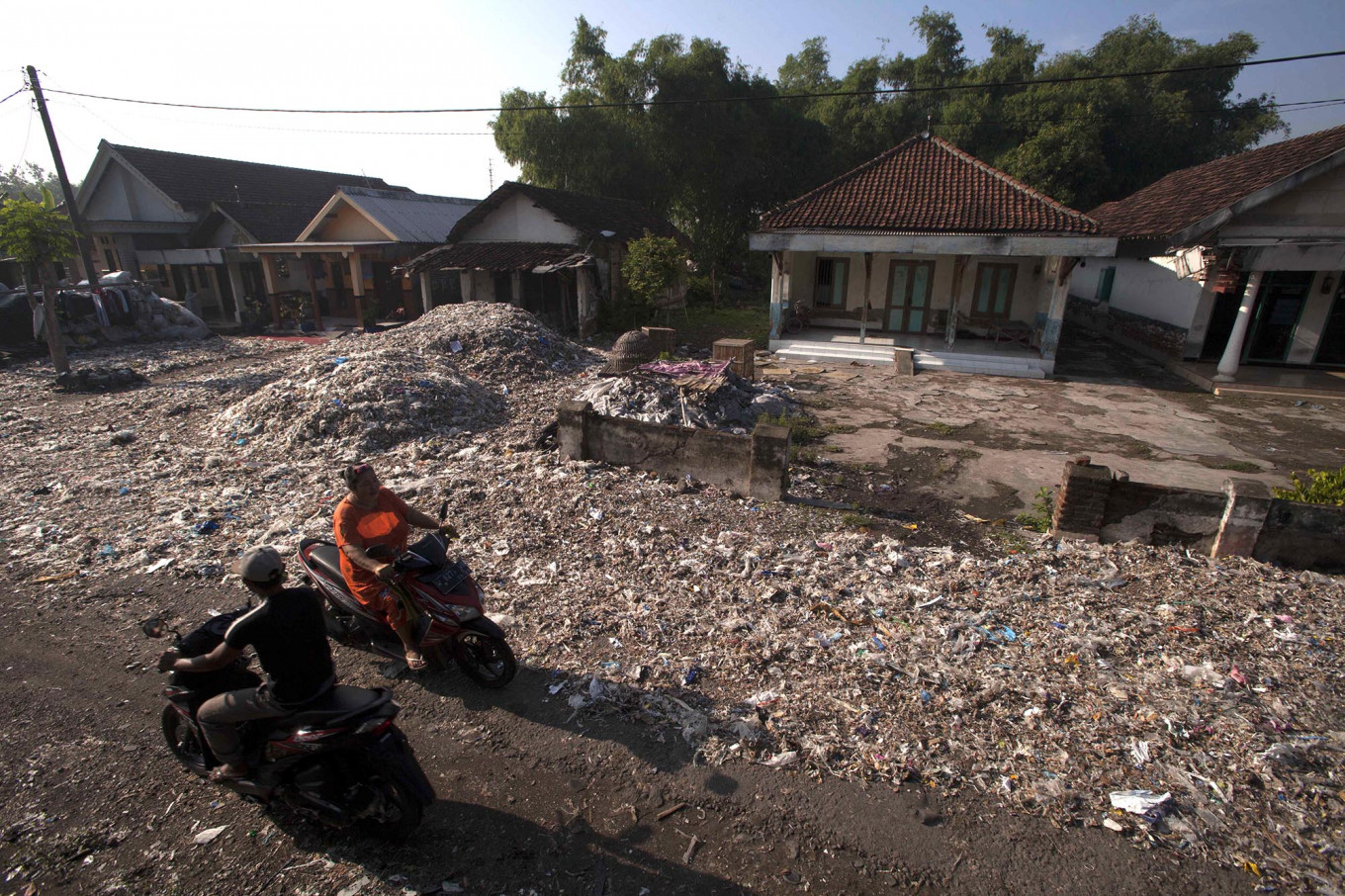 Motorists pass piles of waste on a villager's front yard. JP/Sigit Pamungkas