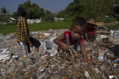 A 3-year-old boy is helping his parents sorting the waste. JP/Sigit Pamungkas