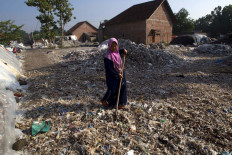 A woman is sundrying the waste in front of her house. JP/Sigit Pamungkas