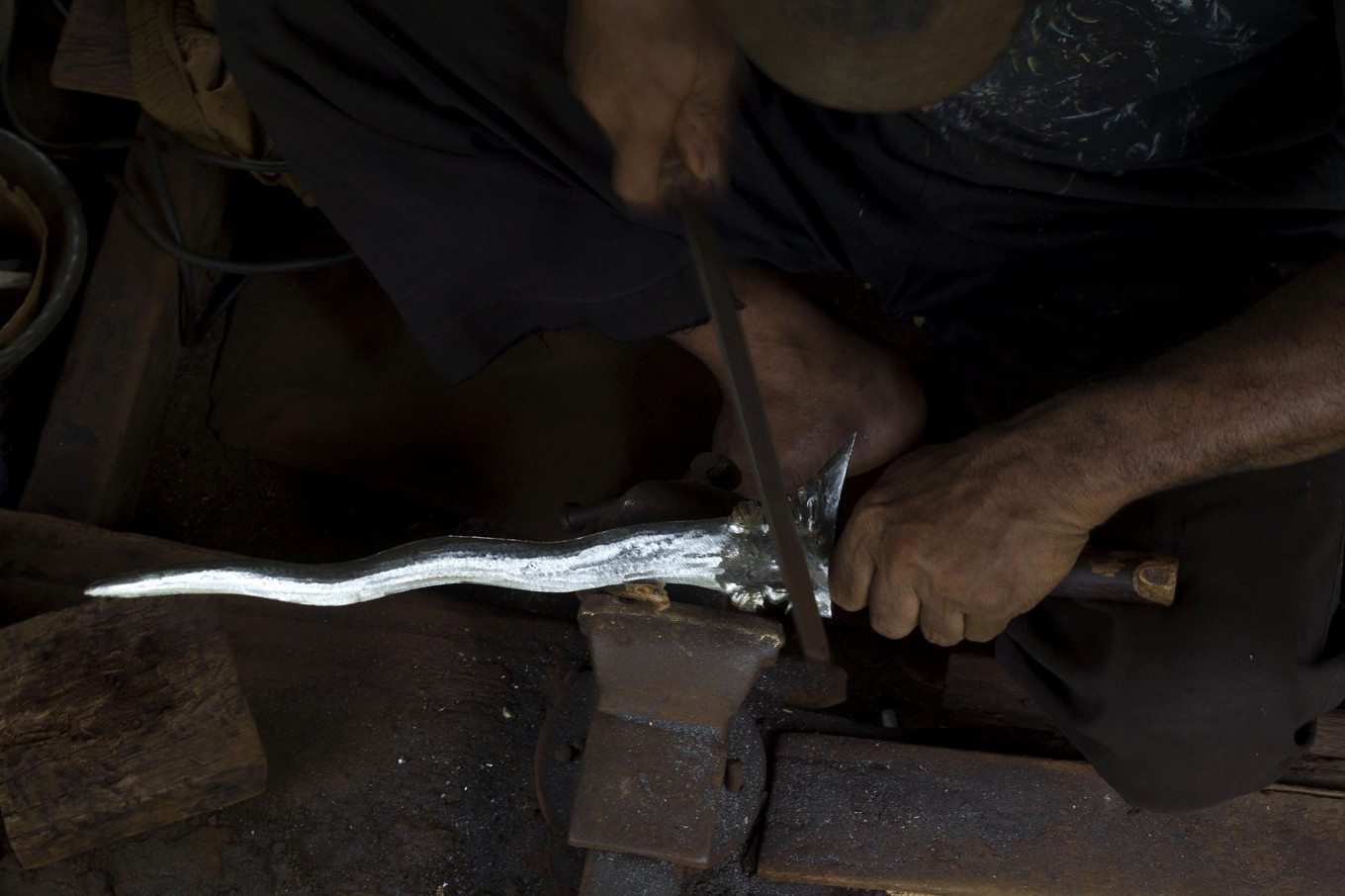 Shining silver: An iron file is used to refine intricate parts of a kris. JP/Sigit Pamungkas