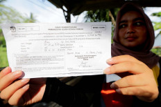 A resident holds up a voting invitation, known as the C6 form, addressed to her father. The forms were handed out by polling station working committees (KPPS) at Ilie village, Banda Aceh, Aceh province, on Saturday. KPPS officers encouraged residents to bring their C6 form on voting day. Those who have yet to receive their invitation should contact KPPS officers at their village. Antara/Irwansyah Putra