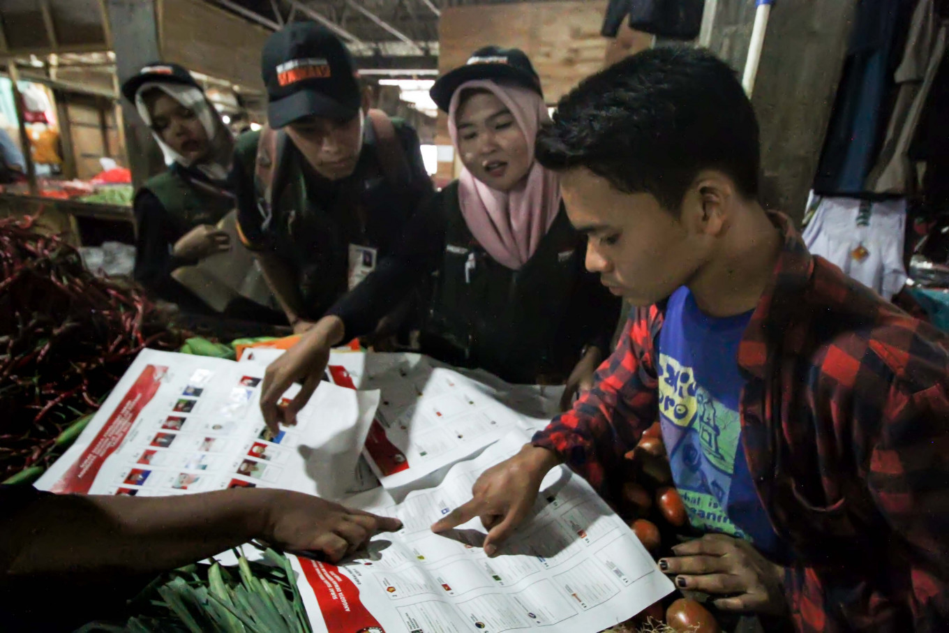 Volunteers at the Lhokseumawe Independent Elections Commission (KIP) show residents ballot samples at the Lhokseumawe Inpres traditional market in Aceh on April 1. The event introduced five types of ballots as well as voting and folding procedures in order to boost voter turnout and spread awareness about residents' voting rights. Antara/Rahmad