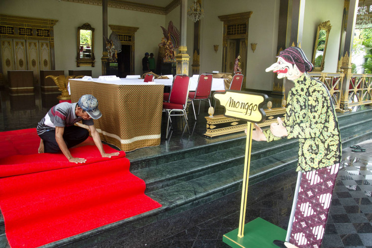 A man prepares polling station TPS 15 in Keraton district, Yogyakarta, on Tuesday. A red carpet was rolled out at the station, where a wood signpost emblazoned with the Javanese greeting