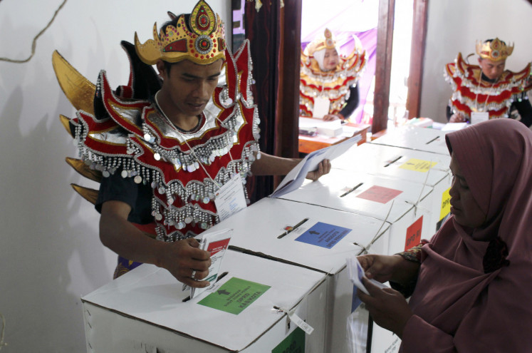 A local poll administrator helps a voter insert ballots into the correct boxes on April 17 in Kemalang district in Klaten, Central Java.