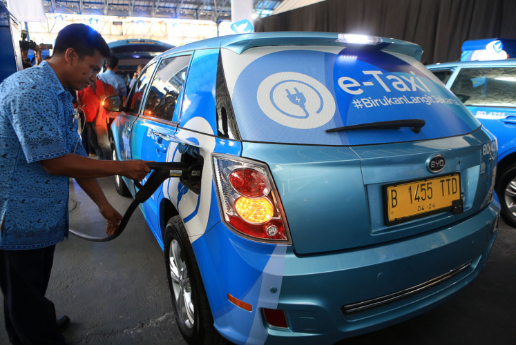 A driver plugs in a Blue Bird e-taxi during the debut of the company's e-taxis in Jakarta on April 22.