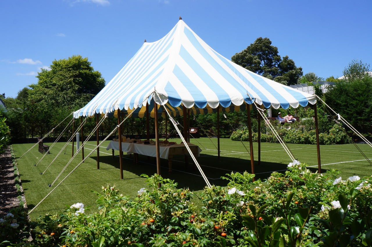 A marquee lends shade to a long dining table laid with mock food and drinks in Mansfield Garden at Hamilton Gardens in Hamilton, New Zealand.