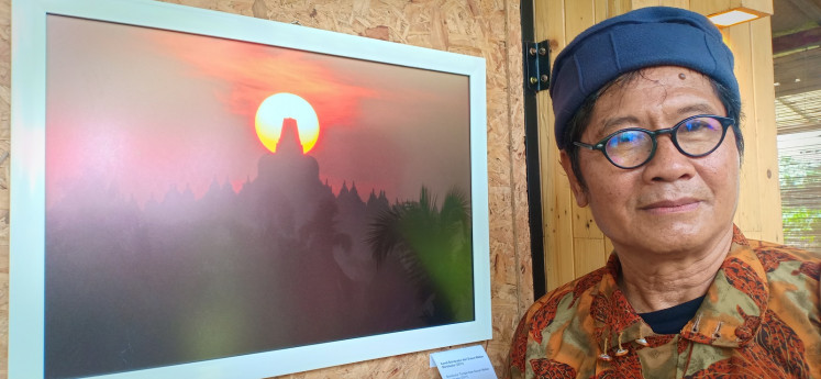 Suparno, a staff member of the Borobudur Conservation Office who is also a photographer, poses with one of his works at an exhibition entitled 'Borobudur in the Eyes of Suparno' at the Nujiwa Community Gallery in Karanganyar, Magelang, Central Java.