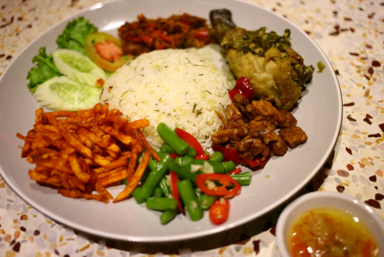 The generous amount of 'nasi campur Ding Dong' comprises seasoned rice with various side dishes, including vegetables and chicken.
