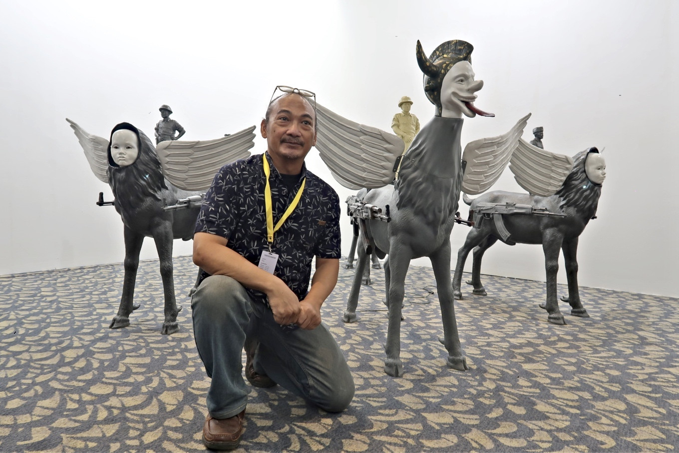 """Renowned contemporary artist Heri Dono poses with his installation titled """"Riding the Tigerish Goat"""