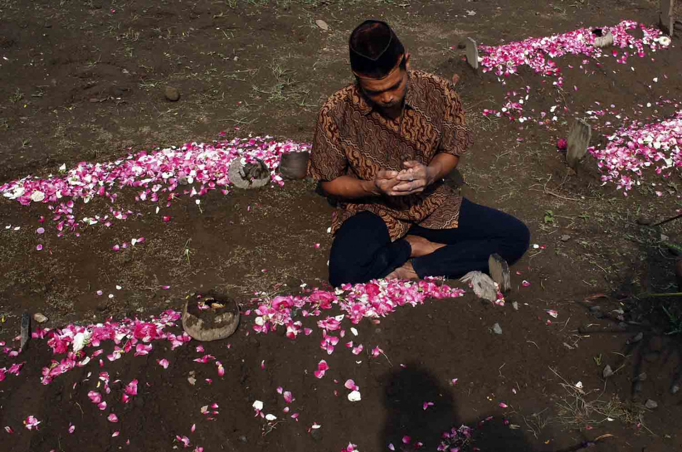 A man prays at a grave during the nyadran ritual in Jogonalan, Klaten, Central Java on April 28. JP/Magnus Hendratmo