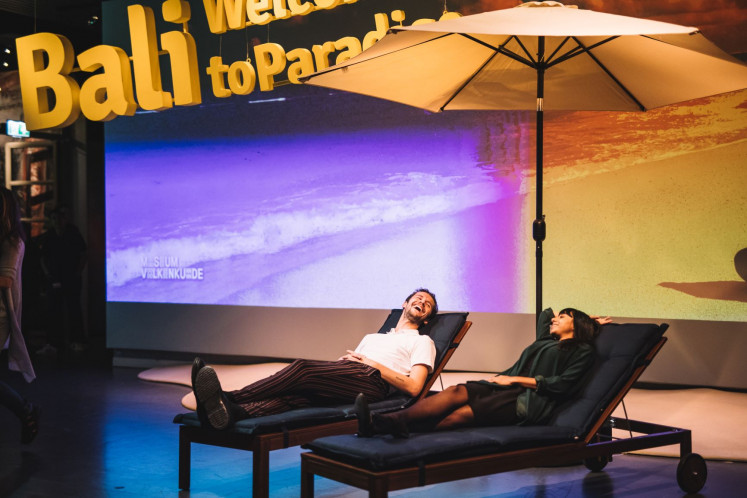 "Imagining paradise: Two visitors lounge in the beach chairs displayed in the entrance hall to ""Bali – Welcome to Paradise"". The exhibit runs through May 26 at the Volkenkunde Museum in Leiden, the Netherlands."
