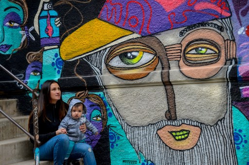 Chilean artist Cynthia Aguilera poses with her son next to a mural made by her in Valparaiso, Chile, on April 09, 2019. Valparaiso is an open-air gallery of graffiti and urban murals.