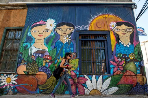 A woman walks past a street mural in Valparaiso, Chile, on April 22, 2019.