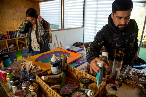 Chilean artists Sammy Espinosa (R) and his wife Cynthia Aguilera work at their workshop in Valparaiso, Chile, on April 22, 2019.
