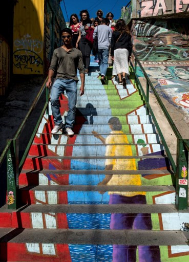 Tourists walk up and down a staircase decorated as a street mural in Valparaiso, Chile, on April 22, 2019.