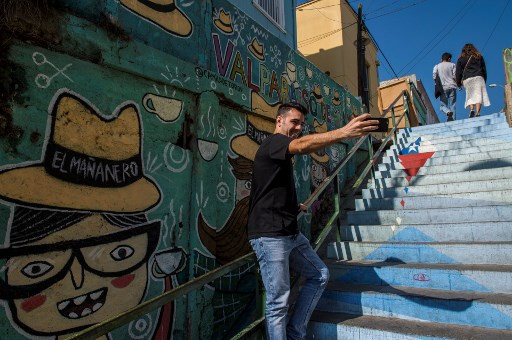 A tourist makes a selfie in front of a street mural in Valparaiso, Chile, on April 22, 2019.