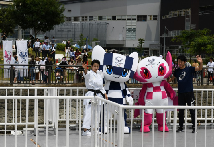 Tokyo 2020 Olympics Games mascots Miraitowa (2nd L) and Someity (2nd R) ride on a boat during a parade in front of spectators with karate practitioner Kiyo Shimizu (L) and para athlete Hajimu Ashida (R) in Tokyo on July 22, 2018. Japanese organisers formally introduced their doe-eyed 2020 Olympic mascots to the world on July 22, christening them with superhero names that could provide a tongue-twisting challenge to some.